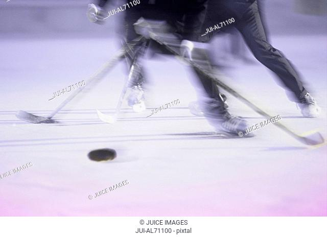 Blurred view of two businessmen racing for the puck in an ice hockey game