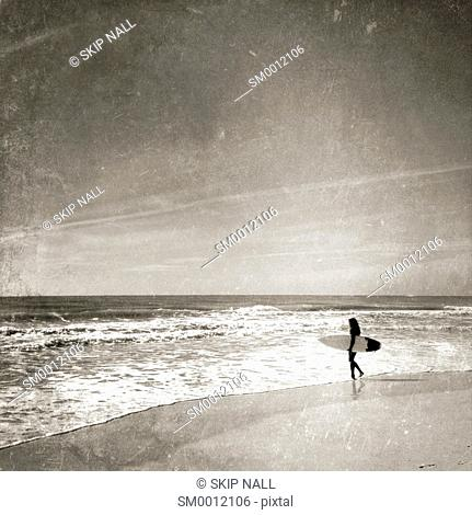 Surfer on the beach about to go surfing and looking at the waves
