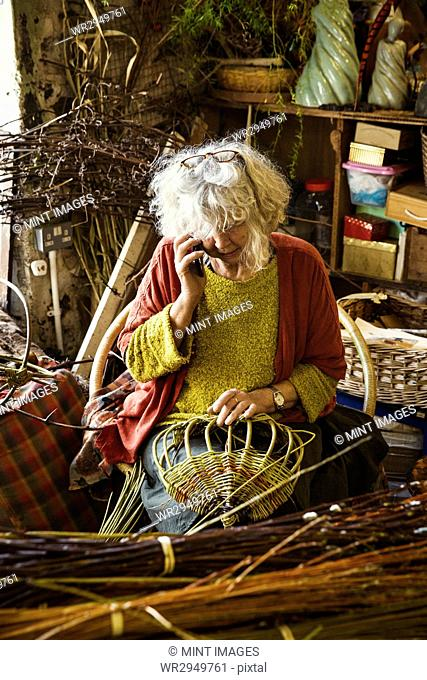 Woman weaving a basket in a weaver's workshop