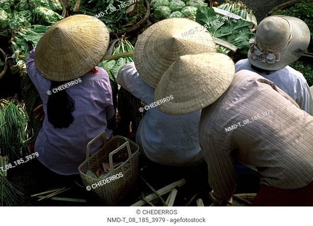 High angle view of four people sitting in a vegetable market, Vietnam