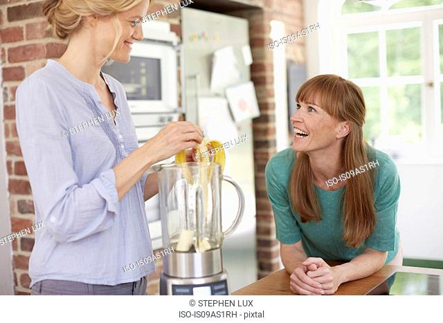 Women using blender and chatting in kitchen
