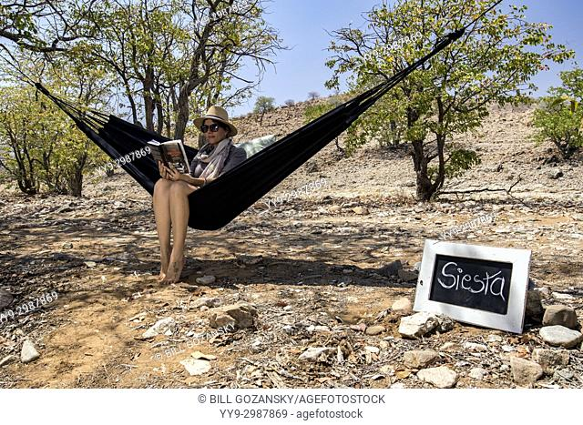 Woman relaxing in Hammock - Huab Under Canvas, Damaraland, Namibia, Africa