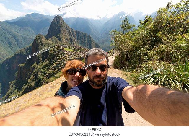 Couple taking selfie on the terraces above Machu Picchu, the most visited travel destination in Peru. Concpet of adventures in South America and people...