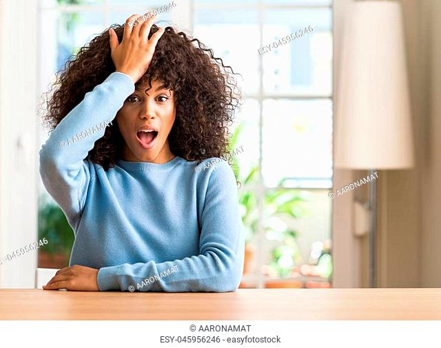 African american woman at home surprised with hand on head for mistake, remember error. Forgot, bad memory concept