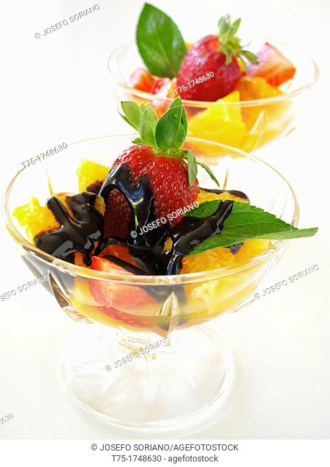 Cup with orange and strawberries with melted chocolate