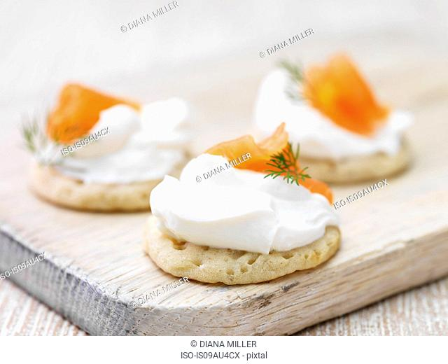 Soft cheese and smoked salmon garnished with dill on blini