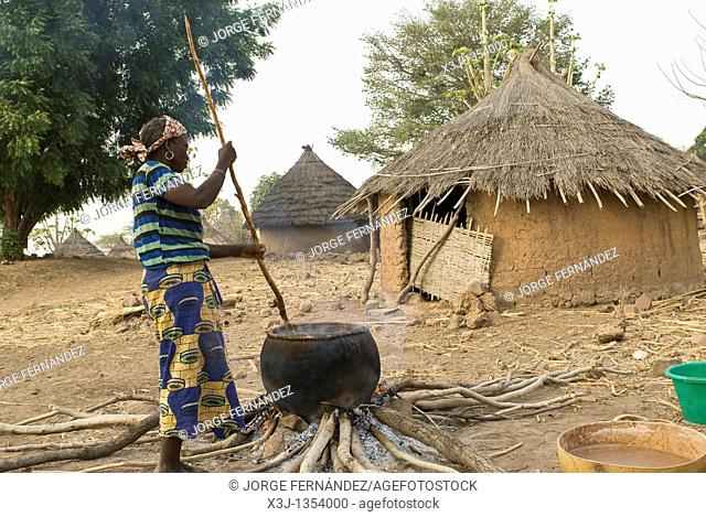 African bedik women cooking crushed peanuts on the fire, Iwol village, Bassari country, Senegal, Africa