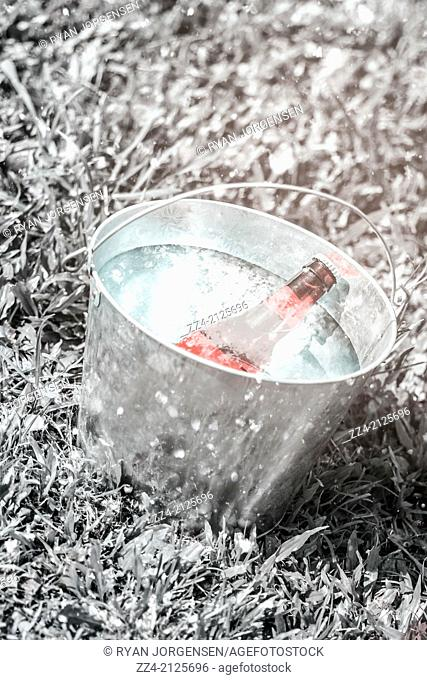 Creative still life image of a frosty cold beer bucket filled with ice sitting on white grass underneath falling snow at winter music festival