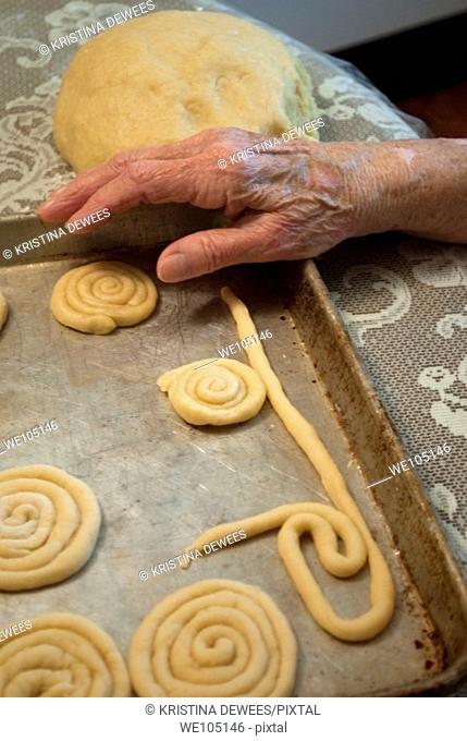 An old woman's hand resting against a tray of cookies