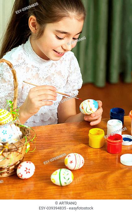 beautiful girl colored Easter eggs sitting at the table