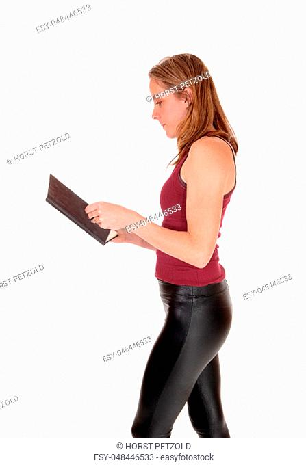 A young slim woman standing in a black leather pants and burgundy.top in profile reading in her book, isolated for white background