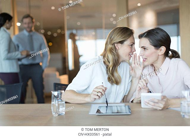 Businesswomen with digital tablets whispering in conference room meeting