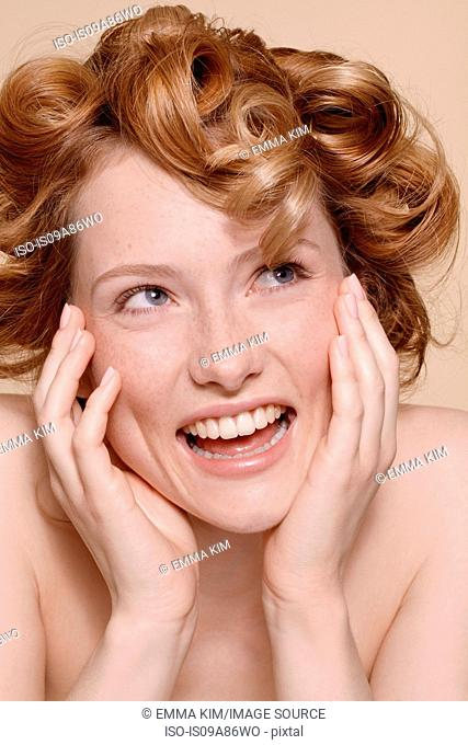 Young woman with curly red hair laughing