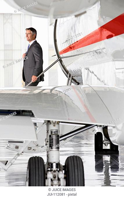 Businessman exiting on stairs of private jet