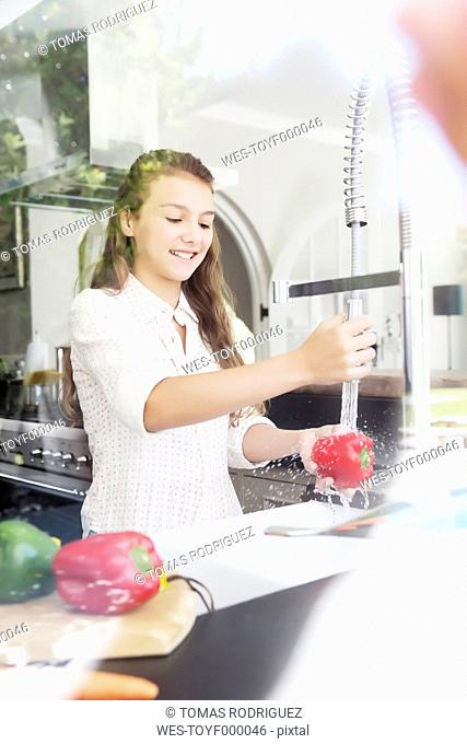 Girl washing vegetables in kitchen