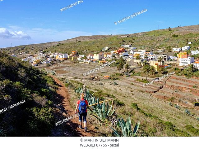 Spain, Canary Islands, La Gomera, Valle Gran Rey, Arure, back view of hiking mature woman