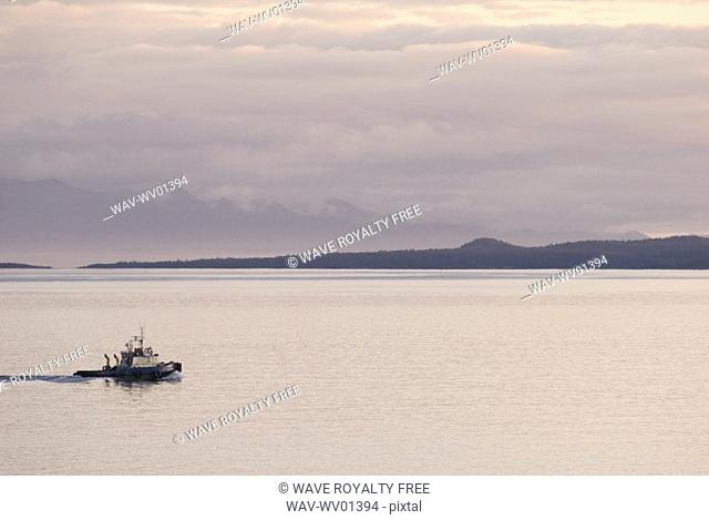 A Tugboat passes the Dallas Road Waterfront in Victoria, BC