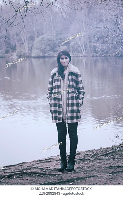 Beautiful Asian woman wearing a coat standing by the lake