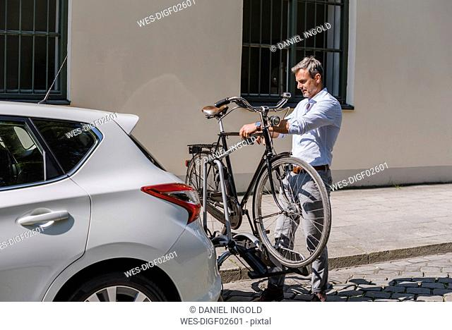 Man fixing bicycle on trailer at car