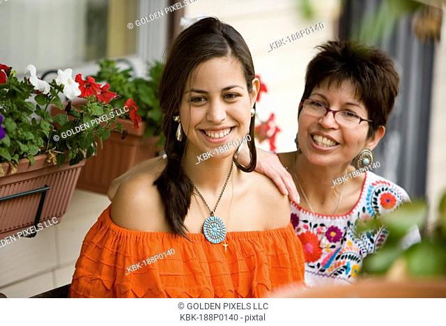Mexican mother and daughter sitting together on front porch of house