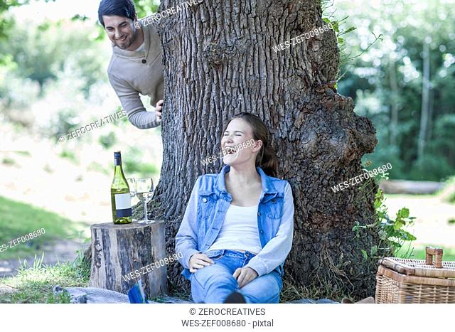Playful young couple having a picnic with white wine