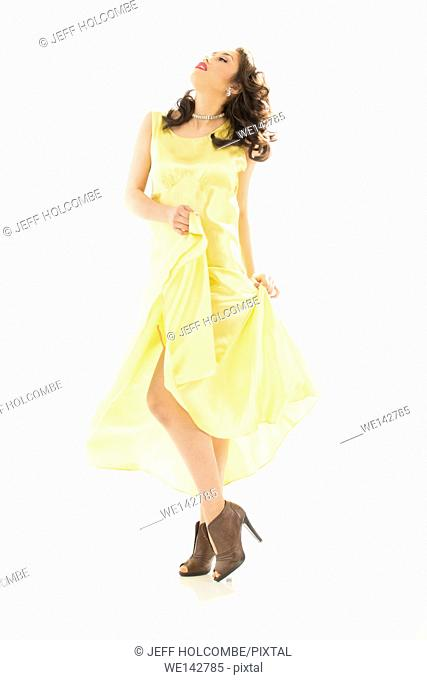 Profile of beautiful young woman in vintage yellow dress, full length in brown heels,head tilted back