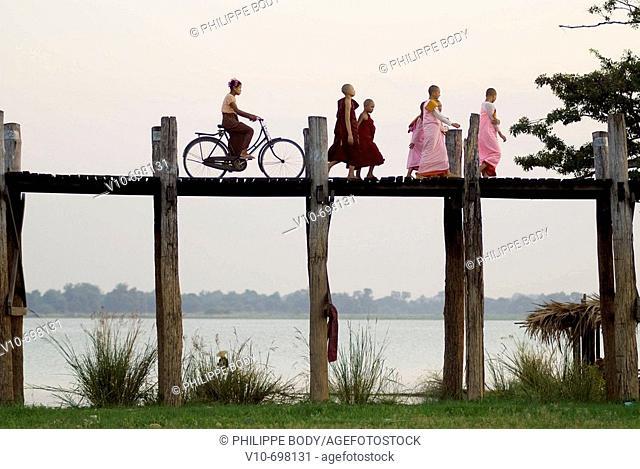 Buddhist monks and nuns on the U Bein bridge in teak wood in the old royal city of Amarapura near Mandalay, Myanmar