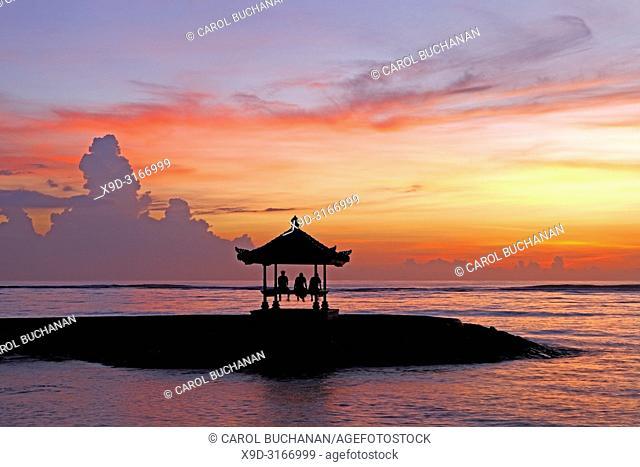 Three people sitting in a Balinese Pagoda on Sanur Beach at Sunrise, Sanur Beach, Bali, Indonesia