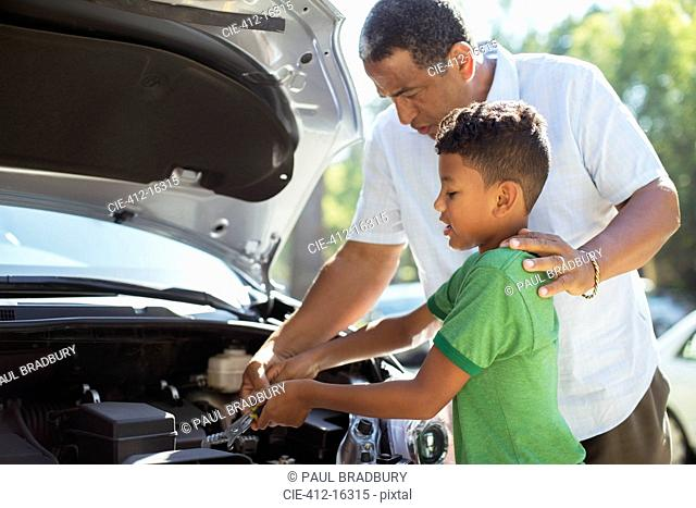 Grandfather and grandson repairing car engine