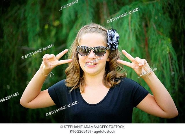 young girl smiling at the camera wearing sunglasses with peace sign fingers