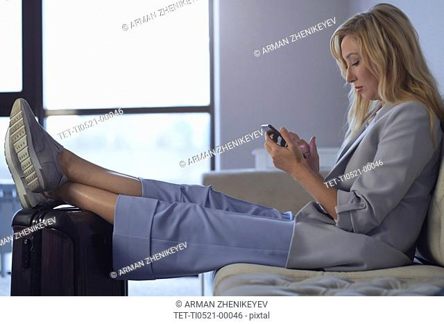 Businesswoman with feet up on luggage in airport lounge