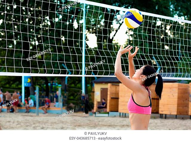 Slender brunette woman playing volleyball near the net on the beach. Space for text