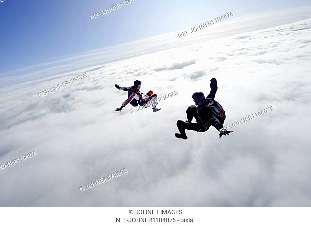 Two people flying above clouds