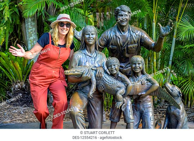 Tourist with statue of Irwin family at the zoo; Beerway, Queensland, Australia