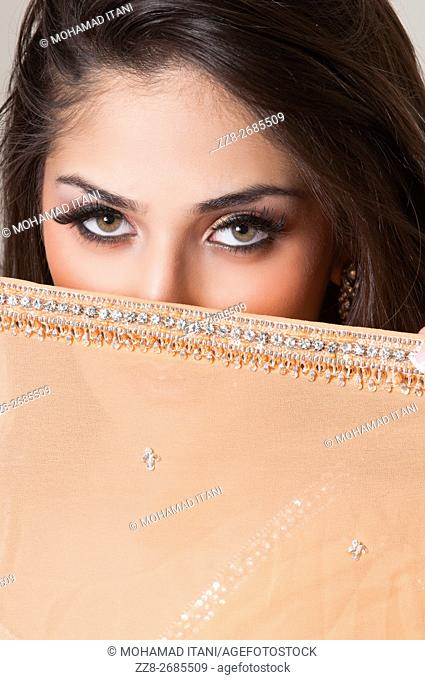Beautiful Indian woman hiding her face with a scarf