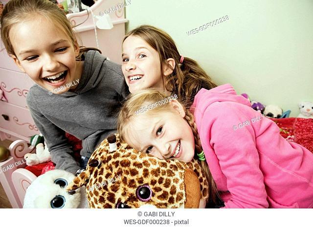 Three playful girls on bed