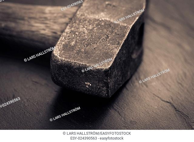 Vintage hammer lying on stone surface. Conceptual image of home improvement, DIY and carpentry