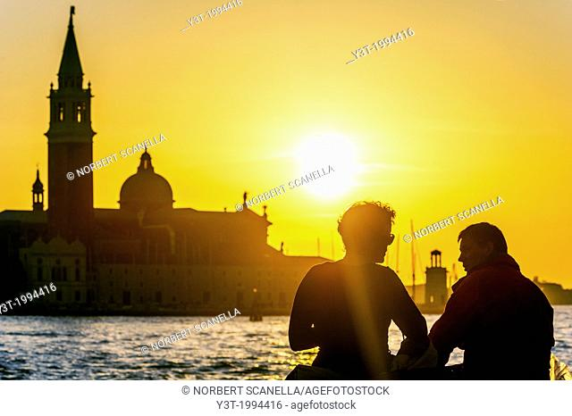Europe, Italy, Veneto, Venice, classified as World Heritage by UNESCO. Tourists in front of the island San Giorgio Maggiore at sunset