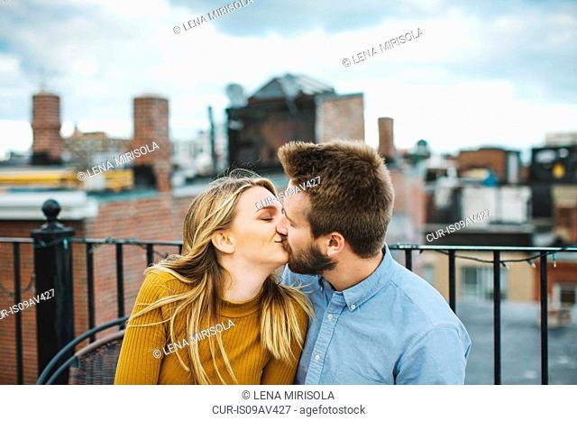 Romantic young couple kissing on city rooftop terrace