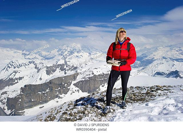 A women in high snowy mountains using a map and cmpass for orienteering