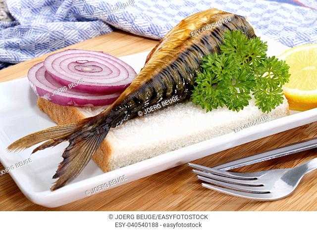 smoked scottish mackerel served on a plate with onion, parsley and lemon