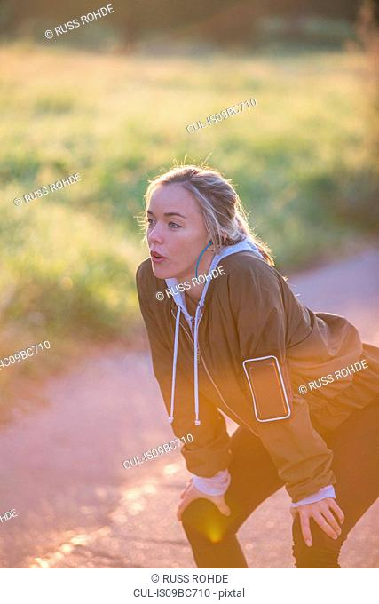 Young woman outdoors, taking a break from exercising, hands on knees
