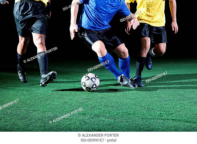Soccer players tackling on pitch, low section