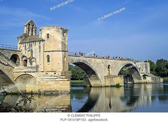 Tourists in summer visiting the Pont Saint-Bénézet / Pont d'Avignon over the river Rhône, Avignon, Vaucluse, Provence-Alpes-Côte d'Azur, France