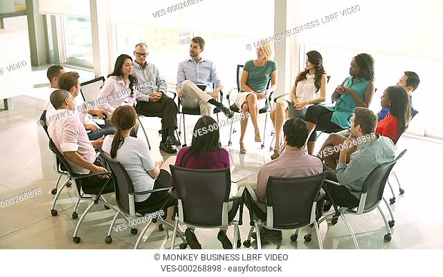 Elevated view as people discuss problems with others seated in a circle around them on chairs .Shot on Sony FS700 in PAL format at a frame rate of 25fps