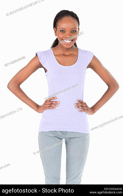 Close up of young woman with arms akimbo on white background