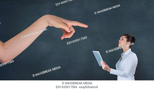 Hand pointing at business woman holding a tablet against blue background