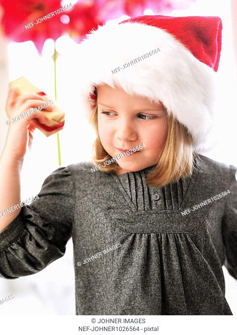 Sweden, Stockholm, girl wearing santa hat holding christmas gift