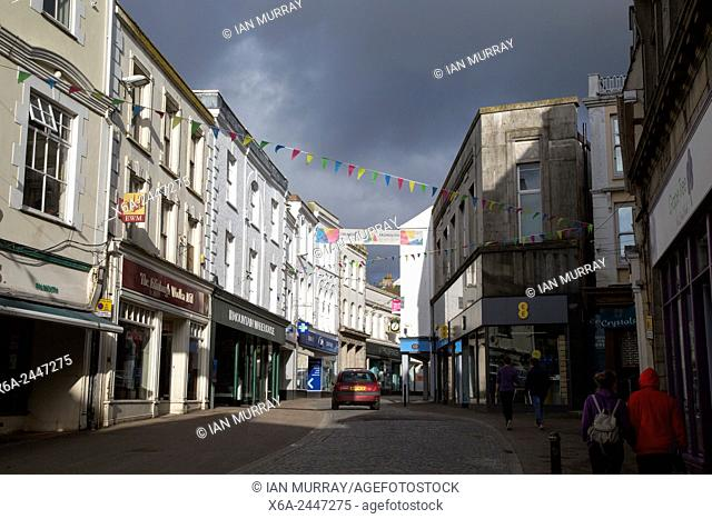 Threatening grey rain clouds over town centre street, Falmouth, Cornwall, England