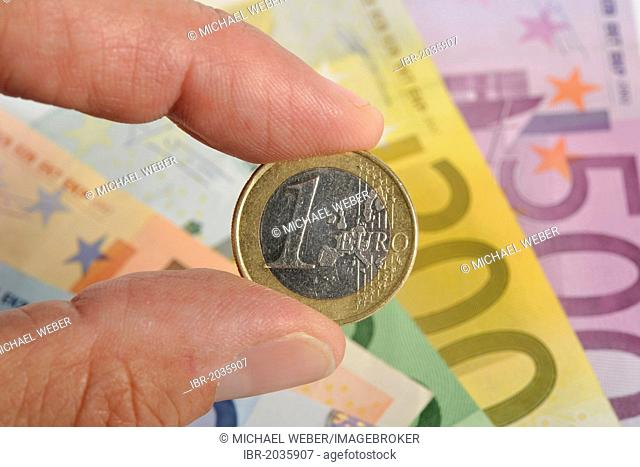 Fingers holding a 1-euro coin in front of a fan of various euro banknotes